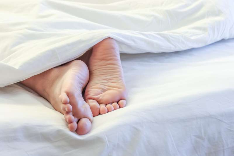 a person on a bed: A stock image shows a person in bed. A 43-year-old man suffered an immune response to his bird feather-filled bedding.
