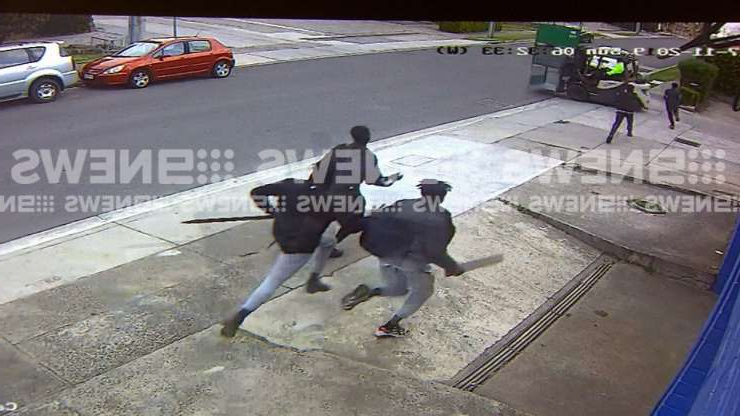 a person sitting in a parking lot: CCTV shows a gang of youths running from the property with wooden boards in their hands.