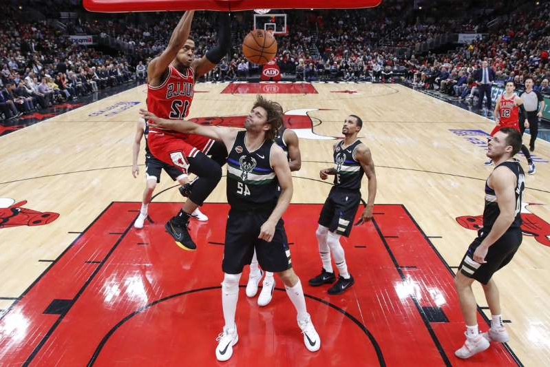 a person standing in front of a crowd: Chicago Bulls forward Daniel Gafford (12) dunks the ball against Milwaukee Bucks center Robin Lopez (42) during the first half at United Center on November 18, 2019.