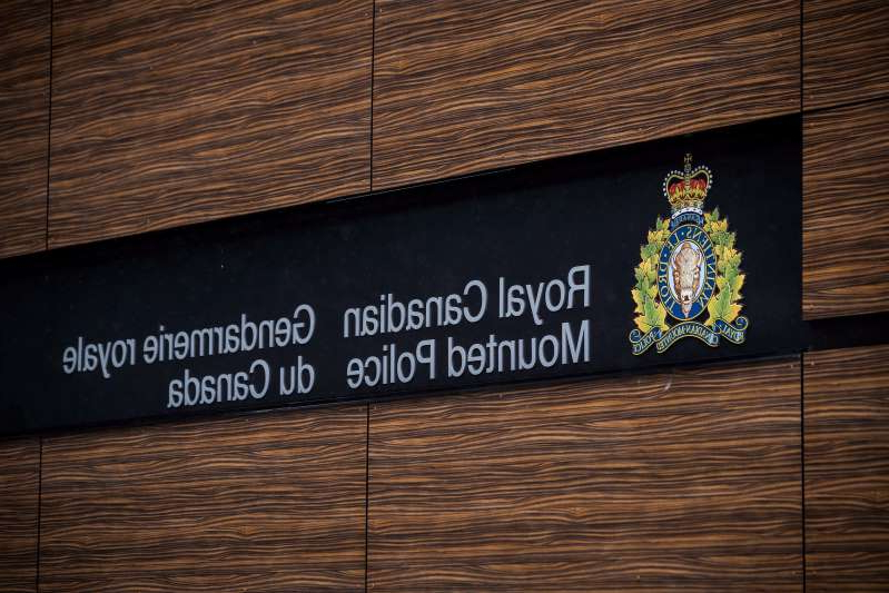 a sign on the side of a building: The RCMP logo is seen outside Royal Canadian Mounted Police