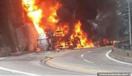 a sign over a fire: The tanker truck explodes after rolling onto its side on the SP-99 road near Caraguatatuba in Brazil, on Monday. The driver appeared to take the bend too quickly and was killed in the accident