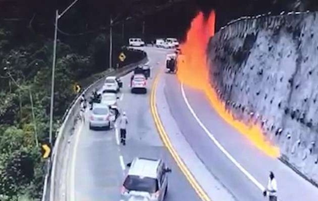 a train driving down the road: Onlookers watch in horror as the fireball erupts and sends a jet of flame shooting along the side of the road