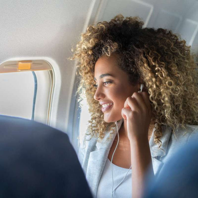 a woman talking on a cell phone: Here's How to Prevent Aching Legs and Joints on Your Next Long Flight