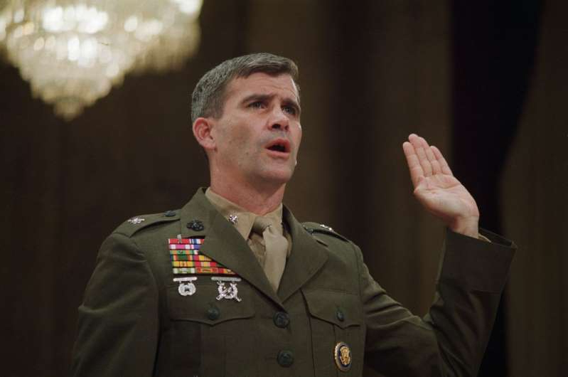 Oliver North wearing a suit and tie: Oliver North, dressed in full military uniform, is sworn in as witness during the 1987 Iran-Contra hearings.