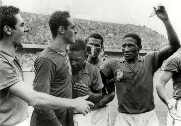 Slide 3 of 18: Pele cries on the shoulder of goalkeeper Gilmar dos Santos Neves after Brazil won the World Cup 1958 by defeating Sweden with a score of 5-2.