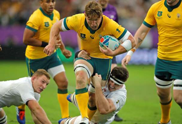 Slide 38 of 100: Australia's Michael Hooper, center, runs at England's defenders during the Rugby World Cup quarterfinal match at Oita Stadium in Oita, Japan, Saturday, Oct. 19, 2019. (AP Photo/Christophe Ena)