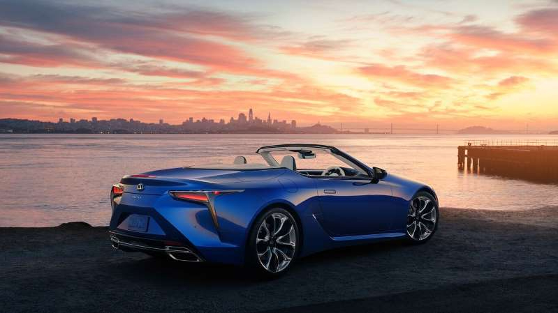 a blue car parked in front of a body of water: 2021 Lexus LC500 Convertible rear three quarter