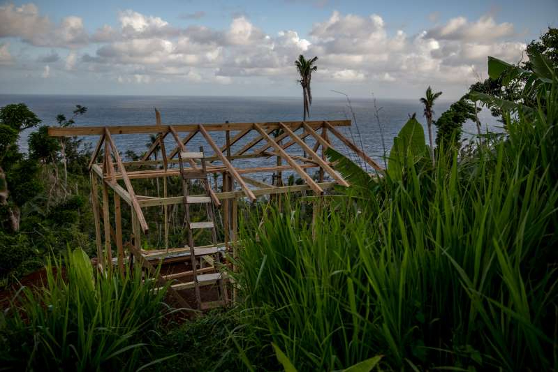 a bridge over a body of water: Eight months after Hurricane Maria hit Dominica, a house is under construction in the Kalinago territory where the Caribbean's last indigenous people live. Five hundred homes have been rebuilt after Maria and 1,000 are slated for construction.