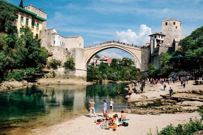 a castle like building with people in the water: A replica of the 16th-century Stari Most (Old Bridge) spans the Neretva River in Mostar, in the country of Bosnia and Herzegovina.