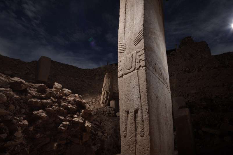 a church with a mountain in the background: Much of the massive Göbekli Tepe archaeological site, in Turkey, remains a mystery. These pillars, dating from about 11,600 years ago, may represent priestly dancers.