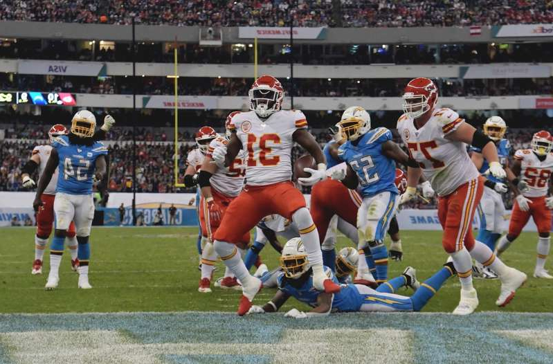 a group of football players on a field: Kansas City Chiefs running back Darrel Williams (31) celebrates after scoring on a 6-yard touchdown run in the third quarter against the Los Angeles Chargersduring an NFL International Series game at Estadio Azteca on November 18, 2019.