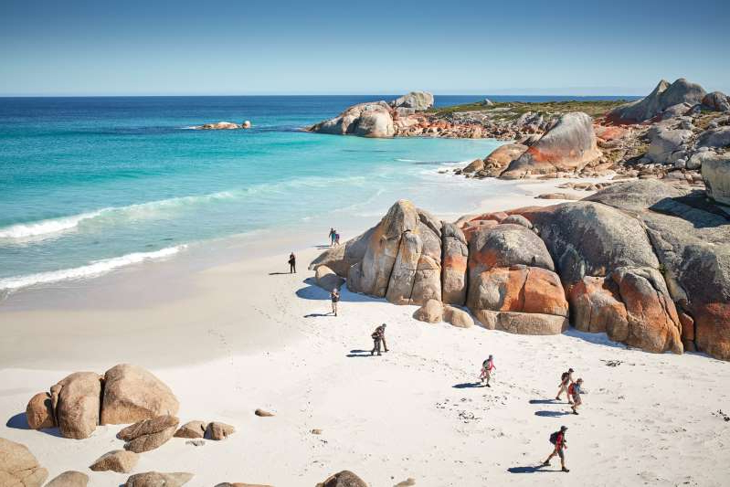 a group of people on a rocky beach: The Bay of Fires, on Tasmania's northeastern coast, got its name from the Aboriginal campfires spotted by British seafarers—but it could also apply to its orange lichen-covered boulders.