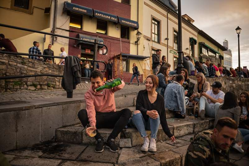 a group of people on a sidewalk: In Spain, locals gather around Gijón's old port where local sidra—cider—is poured into a glass from up high, the Asturian way, a maneuver intended to create froth and open up flavors.