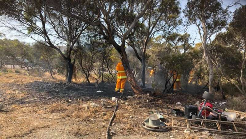 a group of people sitting in a tree: CFS officers attended a flare-up near Port Lincoln which has been extinguished. (Supplied: Toni Castley)