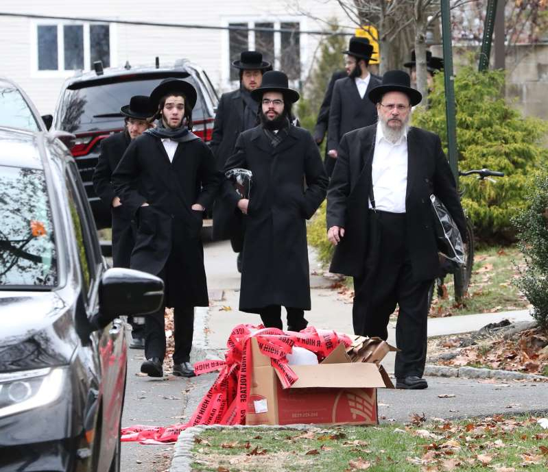a group of people standing next to a car: People walk by the scene of a stabbing on Howard Dr. In Monsey Nov. 20, 2019.