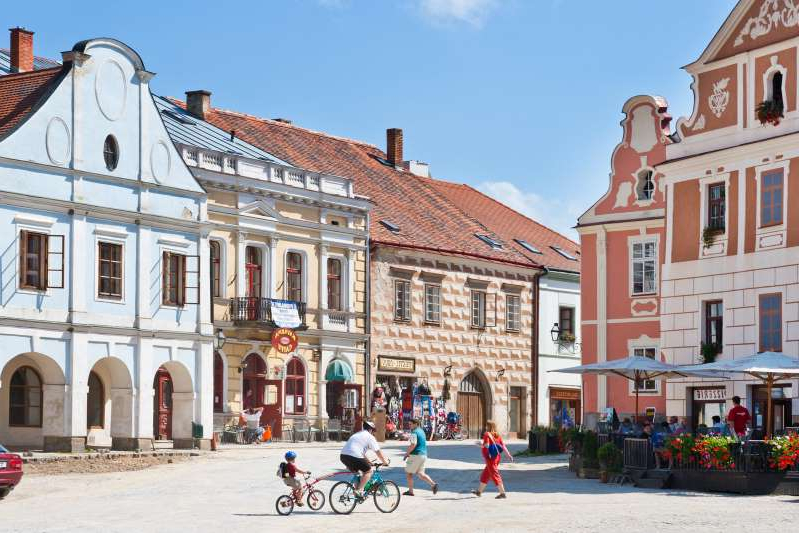 a group of people walking in front of a building: In Czechia, Telč's main square is lined with pastel-hued Renaissance and baroque houses.