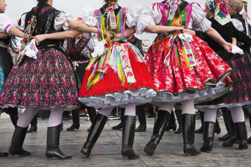 a group of people wearing costumes: In the UNESCO World Heritage site of Hollókő, Hungary, locals mark Easter with Mass, a procession, and folk dances with girls wearing brightly colored traditional costumes.