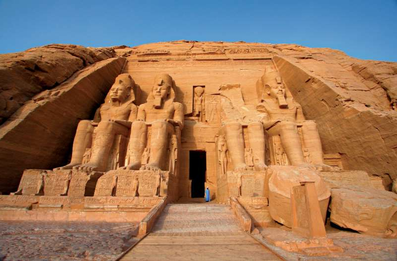 a large brick building with Abu Simbel temples in the background: Colossal statues of Egyptian pharaoh Ramses II guard the entrance to Abu Simbel's main temple.