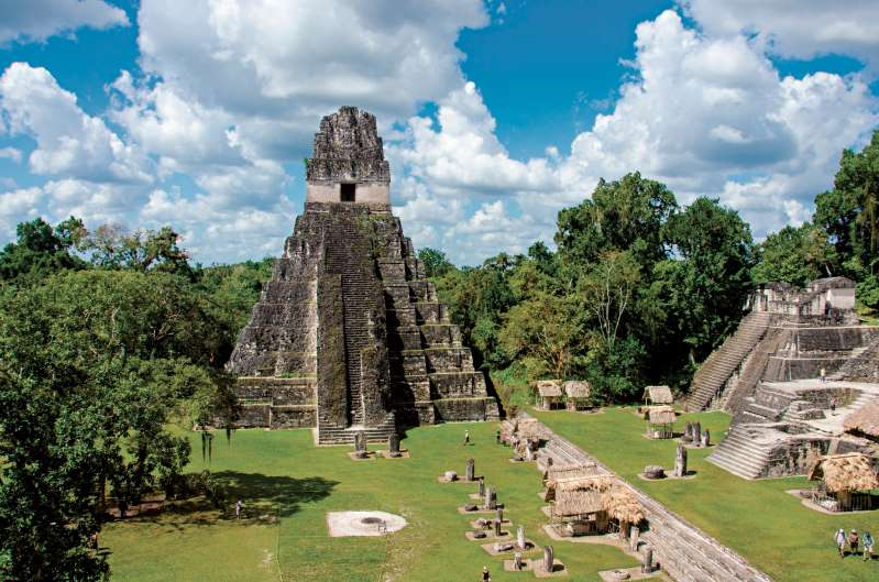a large green field with trees in the background with Tikal in the background: The Temple of the Great Jaguar towers over the main plaza of the ancient Maya city of Tikal, in Guatemala.