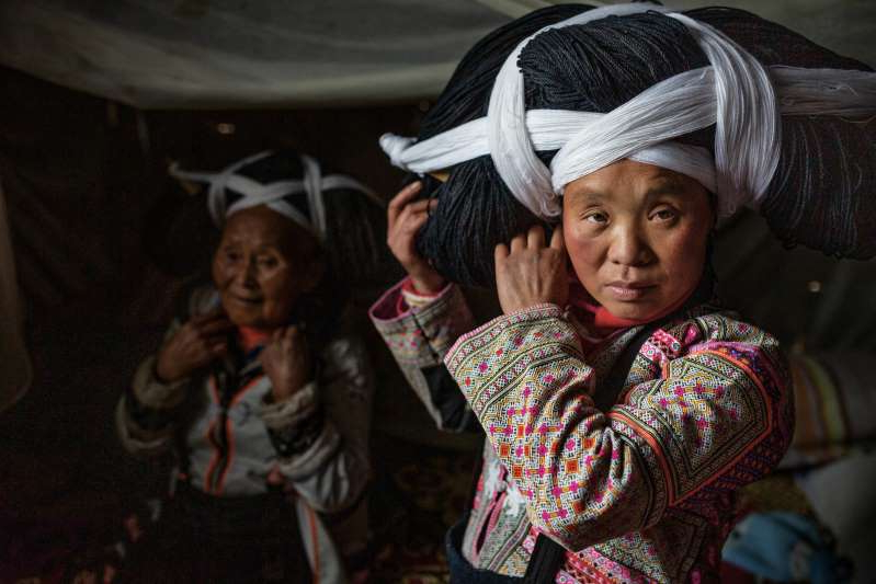 a little girl wearing a hat: Women of the Longhorn Miao tribe in Guizhou province, China, wear elaborate headdresses of linen and wool on special occasions.
