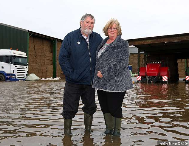 a man and a woman standing in front of water: Left in limbo: Lu and Philip Waite  from Day Villa Farm at Fosterhouses, South Yorkshire, say they still don't know if they are covered for flood damage to their farm