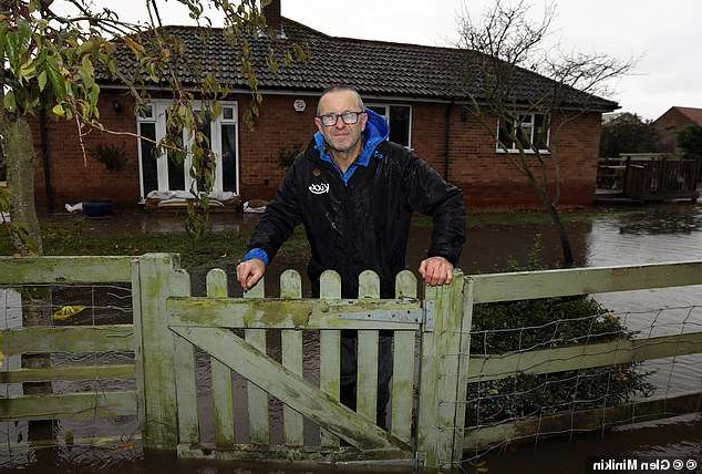 a man standing in front of a fence: Bills: Andy Beaglehole faces a repair bill of up to £45,000 for his three-bedroom bungalow in Fishlake after discovering he wasn't covered for flooding