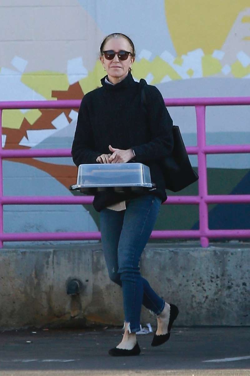 a person sitting on a bench in front of a building: Felicity Huffman leaves The Teen Project building in Los Angeles on Nov. 3, 2019.