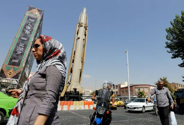 a person standing in a parking lot: A Shahab-3 surface-to-surface missile is on display in a Tehran street exhibition by Iran's Revolutionary Guards in September 2019 marking the anniversary of the Iran-Iraq War