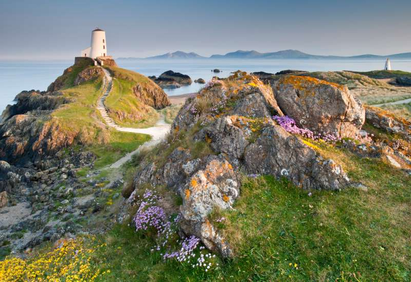 a rocky hill: The Twr Mawr Lighthouse in Anglesey is a scenic stop along the United Kingdom's new North Wales Way.