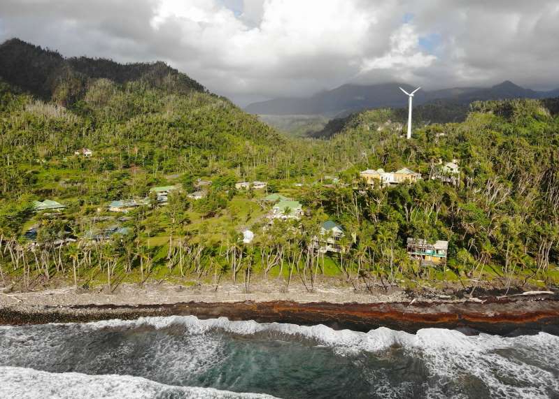 a sign on the side of a mountain: When Hurricane Maria struck Dominica in September 2019, more than 90 percent of the island's structures were destroyed and leaves were ripped from trees. Today, the people of Dominica are rebuilding with the knowledge that climate change could mean a future of storms like Maria.