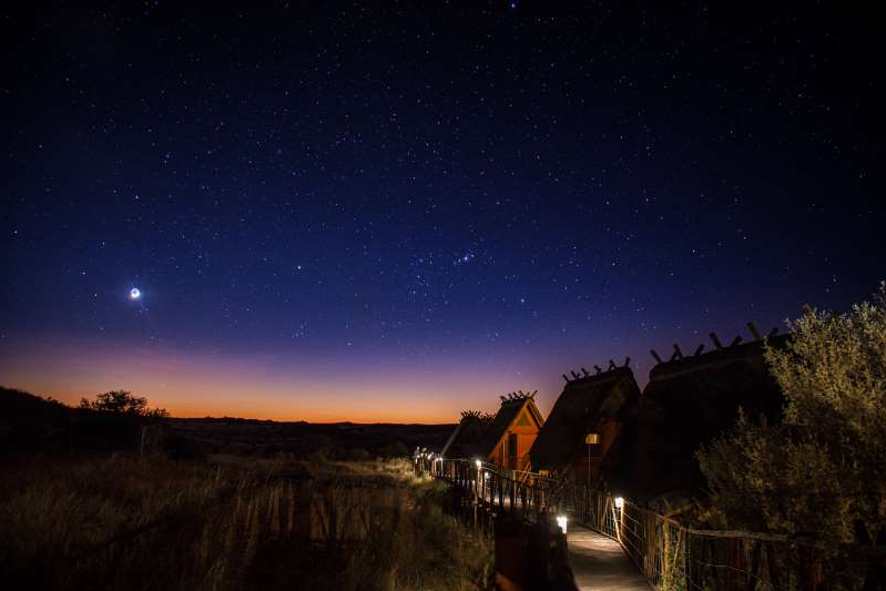 a sunset over a city at night: Inside !Ae!Hai Kalahari Heritage Park, among the world's darkest places, visitors can stay at the 12-chalet !Xaus Lodge and use telescopes on the open deck to observe the Southern Cross and other night-sky wonders.