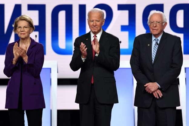 Bernie Sanders, Joe Biden, Elizabeth Warren standing next to a person wearing a suit and tie: (FILES) In this file photo taken on October 15, 2019 (From L) Democratic presidential hopefuls Vermont Senator Bernie Sanders, former US Vice President Joe Biden and Massachusetts Senator Elizabeth Warren arrive onstage for the fourth Democratic primary debate of the 2020 presidential campaign season co-hosted by The New York Times and CNN at Otterbein University in Westerville, Ohio. (Photo by SAUL LOEB / AFP) (Photo by SAUL LOEB/AFP via Getty Images) ORG XMIT: Elizabeth ORIG FILE ID: AFP_1LU5MK