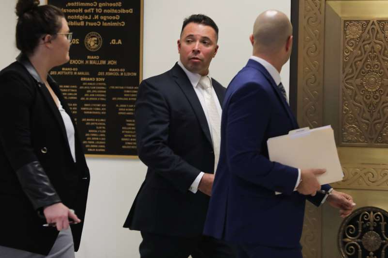 Dante SERVÍN et al. standing next to a person in a suit and tie: Ex-Chicago cop Dante Servin, center, who shot and killed Rekia Boyd walks into the courtroom at Leighton Criminal Courthouse to have his criminal charges expunged, Thursday Nov. 14, 2019.  His case was moved to next week.