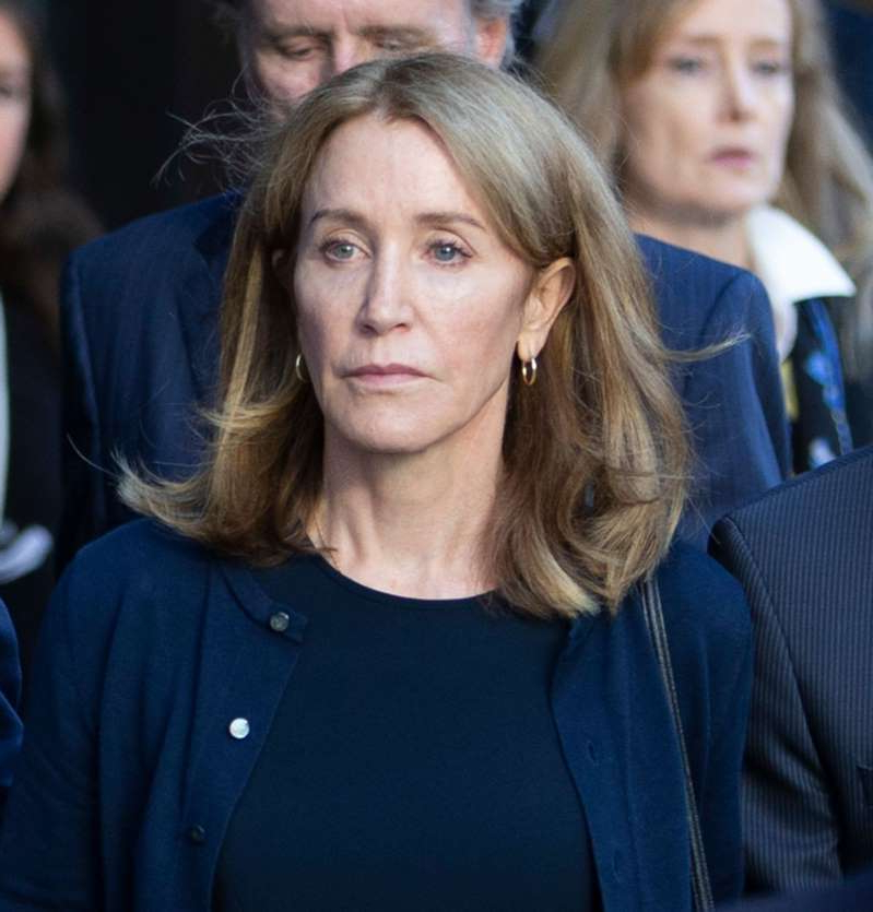 Felicity Huffman et al. posing for the camera: Felicity Huffman leaves the federal courthouse in Boston, Mass., on Sept. 13, 2019.