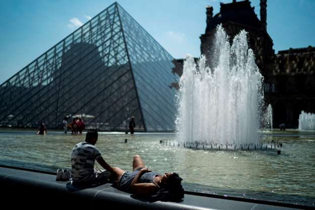 Slide 8 of 9: TOPSHOT - People sunbath in front of the Louvre Pyramid (Pyramide du Louvre) designed by Ieoh Ming Pei during a heatwave in Paris on June 26, 2019. - Forecasters say Europeans will feel sizzling heat this week with temperatures soaring as high as 40 degrees Celsius (104 degrees Fahrenheit) in an