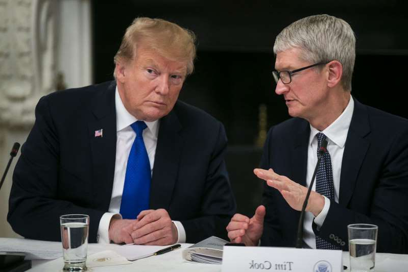 Tim Cook, Donald Trump are posing for a picture: Tim Cook speaks with Donald Trump during an American Workforce Policy Advisory board meeting at the White House in Washington, D.C., on March 6.