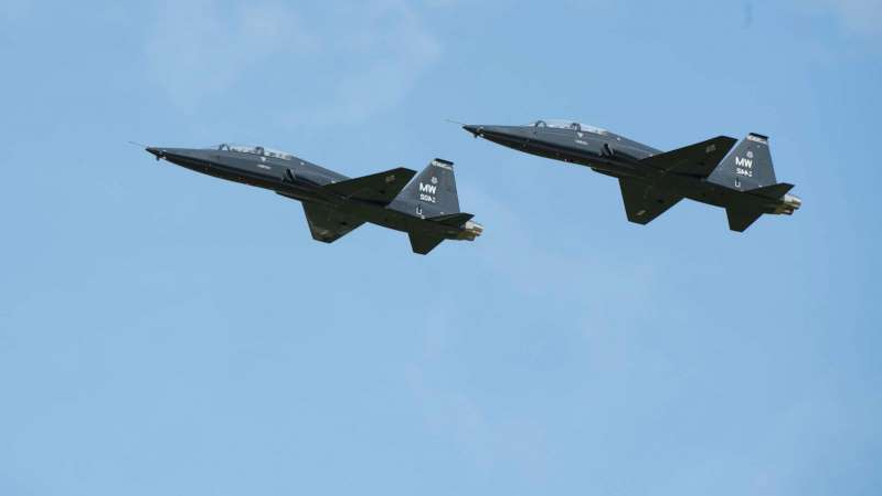 a fighter jet flying through a blue sky: Two T-38 Talons fly in formation over Whiteman Air Force Base in Johnson County, Miss., June 16, 2019.