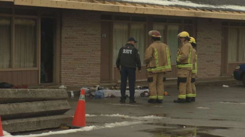 a group of people on a sidewalk: Peterborough Fire Services investigate a fire at a hotel room at the Trentwinds International Centre and Motor Hotel on Wednesday morning.