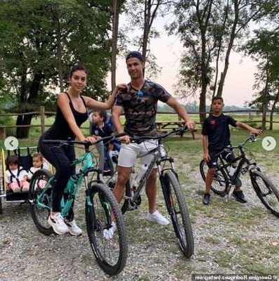a group of people riding on the back of a bicycle: Her love: Georgina has inserted herself smoothly into life with Cristiano and his children Cristiano Jr., nine, two-year-old twins Eva and Mateo, and Alana, 22 months