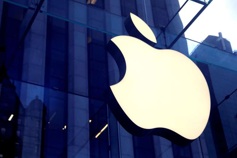 a large white building: FILE PHOTO: The Apple Inc. logo is seen hanging at the entrance to the Apple store on 5th Avenue in New York