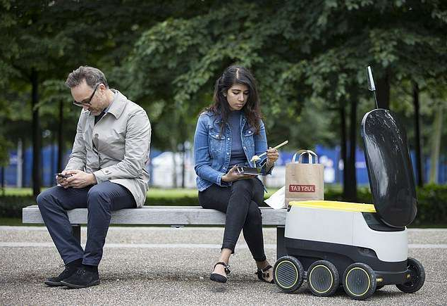 a man and a woman sitting on a bench talking on a cell phone: The self-driving delivery robot by Starship Technologies is designed to carry items within a four-mile radius including packages, groceries and foods, once requested via mobile app. A pilot of the robot pictured above in London on July 5, 2016