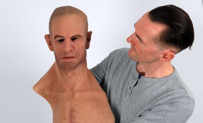 a man looking at the camera: Research Rob Jenkins holds a hyper-realistic mask.