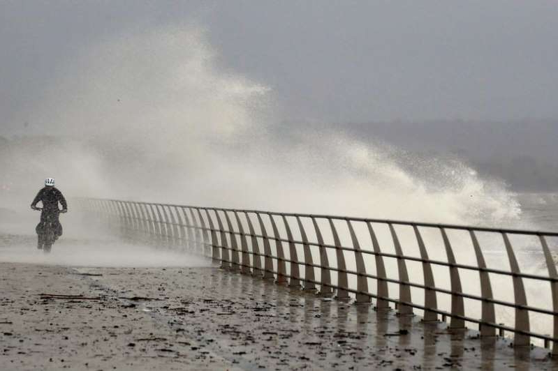 a man standing in front of a pier: Swansea Bay's sea defences protect the prom from the worst weather and highest tides