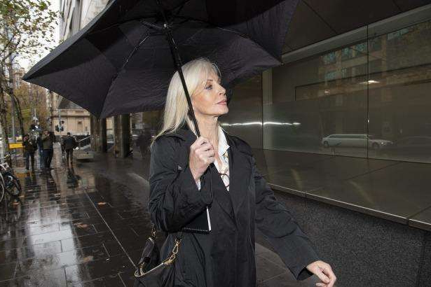 a woman walking in the rain holding an umbrella: Semmens, seen outside court in June,  seemed dismissive of the legal process.