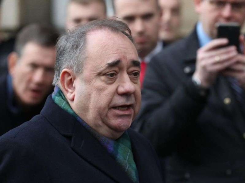 Alex Salmond wearing a suit and tie talking on a cell phone