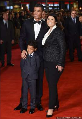 Cristiano Ronaldo wearing a suit and tie standing in front of a crowd: Her dream: The star is famously close to his mother Maria Dolores Aveiro and admits it's her dream for the couple to wed. Pictured in 2015