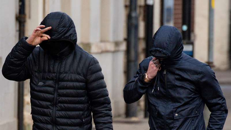 George Powell and Layton Davies cover their faces outside court
