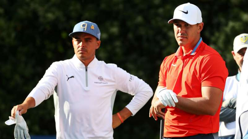 Rickie Fowler wearing a red hat: Brooks Koepka (left) and Rickie Fowler