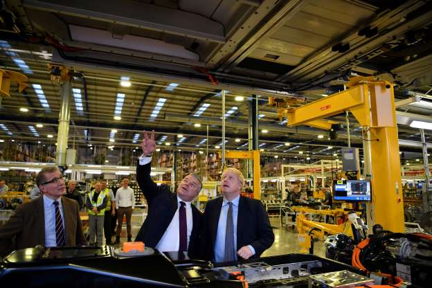 Slide 10 of 31: Britain's Prime Minister Boris Johnson accompanied by LEVC CEO Jorg Hoffman looks at the chassis of an electric taxi during his Conservative party general election campaign visit to the London Electric Vehicle Company (LEVC) in Coventry, Britain November 13, 2019. Ben Stansall/Pool via REUTERS