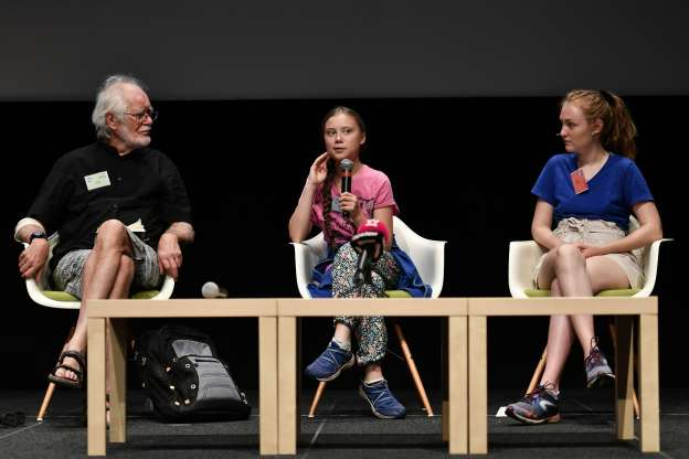 Slide 11 of 14: Swedish climate Activist Greta Thunberg (C) speaks, as she sits between Loukina Tille (L) the organiser of the